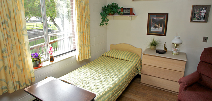 Single occupancy room with cheerful yellow curtains and a yellow bedspread looking out to a yard and trees