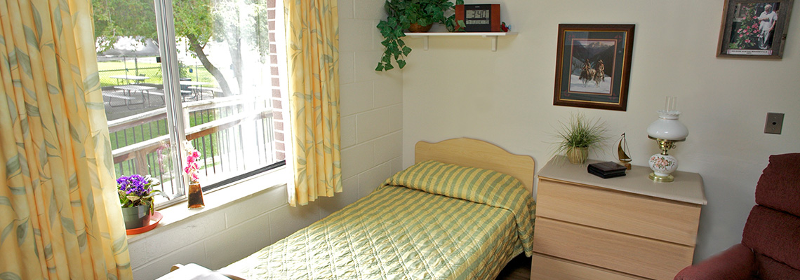 Single occupancy room with cheerful yellow bedspread and curtains