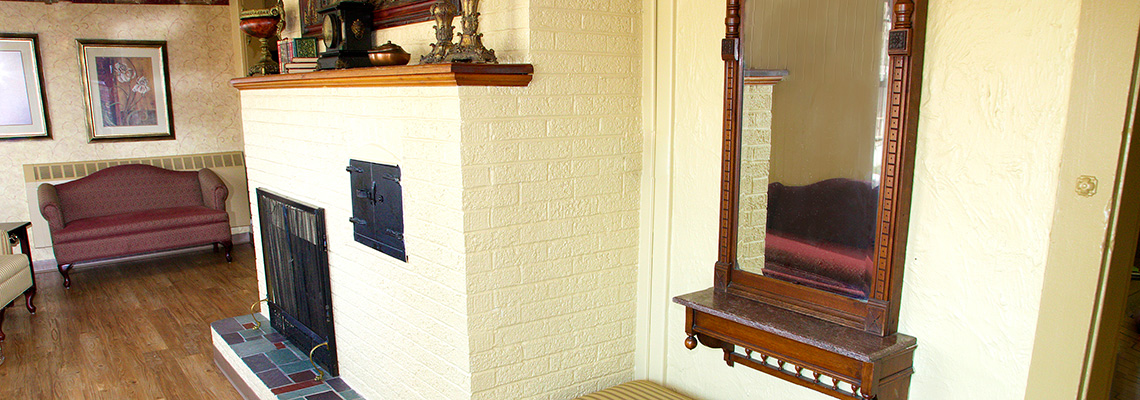 White brick fireplace and burgundy upholstered couch in the waiting area