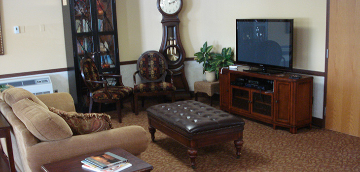 Resident living room with comfortable seating and a flat screen tv.