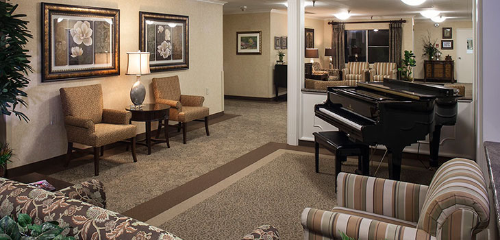 facility living room with piano and chairs