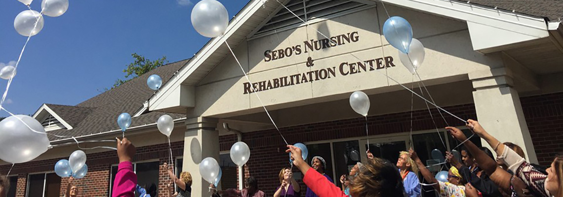 Sebo's Nursing & Rehabilitation Center staff celebrating outside the front entrance
