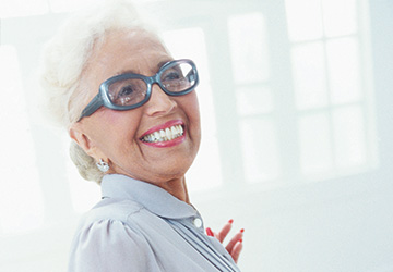 A woman with thick brimmed glasses on smiling.