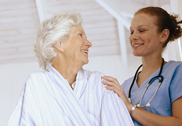 A nurse with a stethoscope around her neck looking down at a patient sitting in bed.