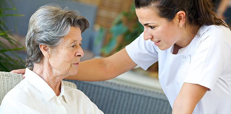 A nurse leaning in to speak with a resident.