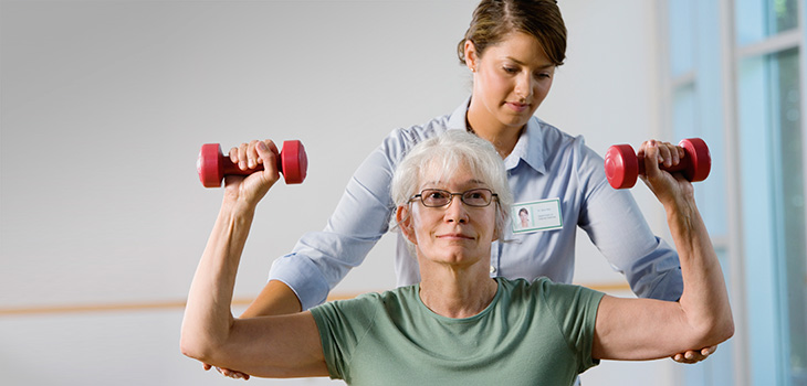 female resident doing physical therapy with a therapist and using small red hand weights