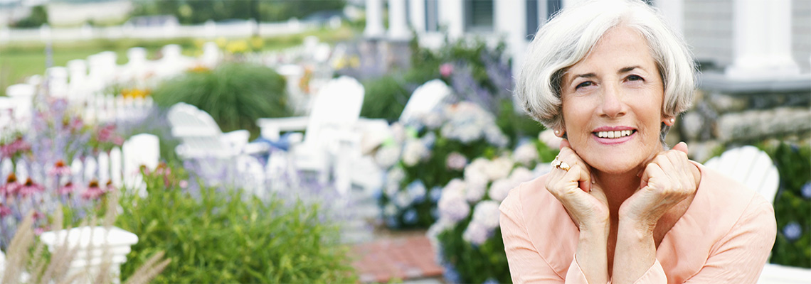 attractive silver-haired woman seated in the garden with a white picket fence