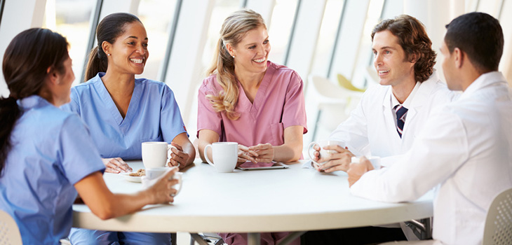 A group of healthcare professionals sitting around a table talking and drinking coffee.