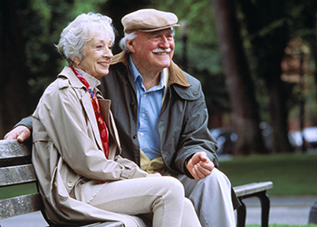 A couple sitting on a bench together smiling in a park.