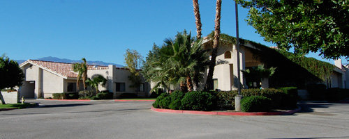 Indio Nursing & Rehabilitation Center building with bushes and palm trees out front.