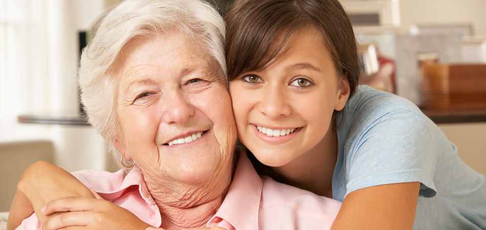 A grandmother and granddaughter smiling together.