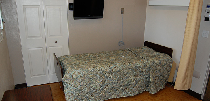 A resident room with flat screen television and closet.