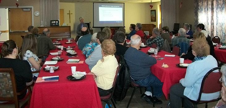 "Speaker showing informative slides at the ""Understanding Alzheimer's Disease"" presentation"