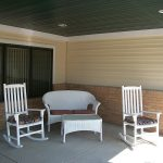 Adirondack chairs and a wicker sofa on a covered outdoor patio area