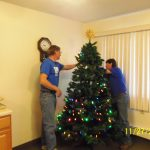Staff members putting the finishing touches on the tree