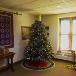 Festively decorated tree with handmade quilt hanging beside it on the wall