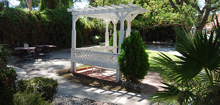 Outside seating area with a gazebo nearby, walking paths and a beautiful garden