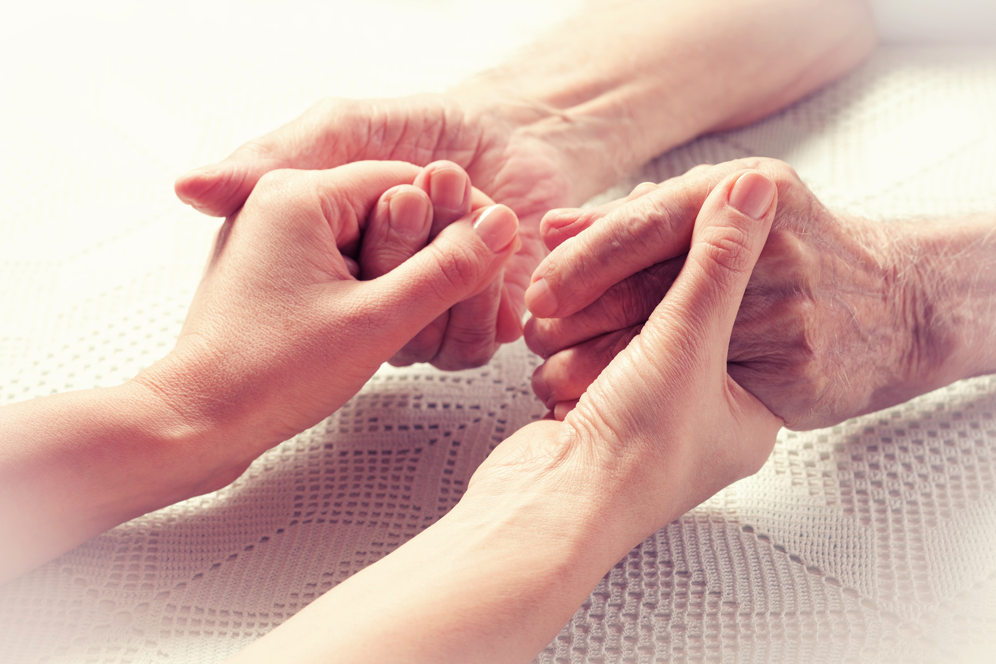 Senior man and caregiver holding hands