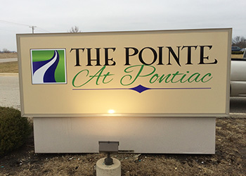 The Pointe at Pontiac sign outside with a light shinning on it
