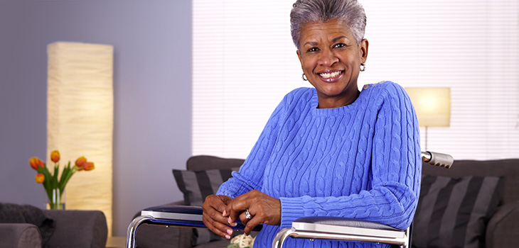 smiling woman seated in a wheelchair wearing a bright blue sweater