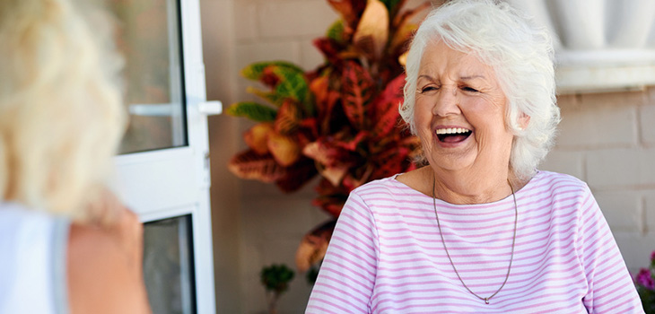 smiling elderly woman seated outside on the patio