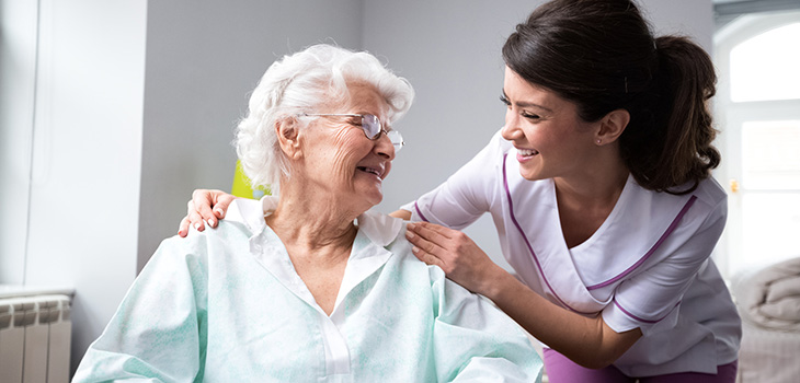 A nurse leading toward a resident with her hands on her shoulders and a big smile on her face
