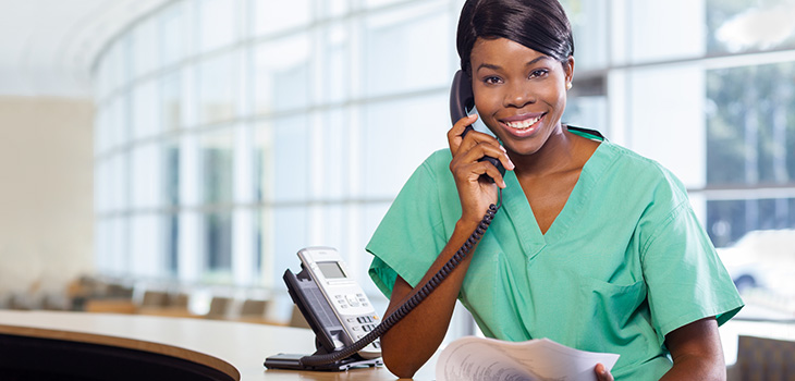 A woman in scrubs on the telephone smiling