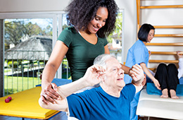 A rehab staff member assisting a patient with exercises