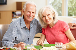A couple sitting together smiling with a table set in front of them