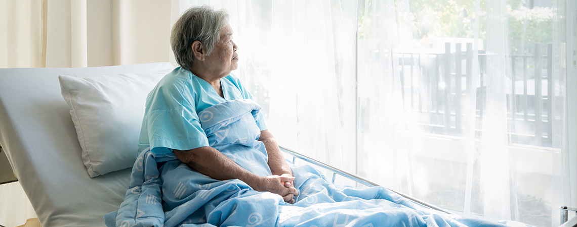 A senior sitting up in bed staring out the window