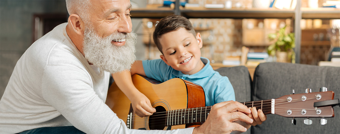 A senior teaching a young boy to play the guitar