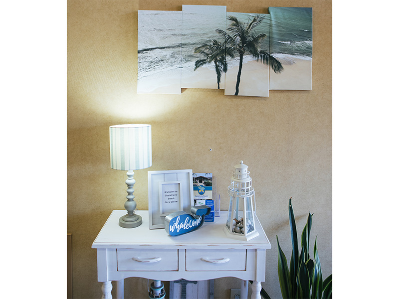 Entrance table with a light on, a small lighthouse and a whale shape beside a frame and under a beach themed image.
