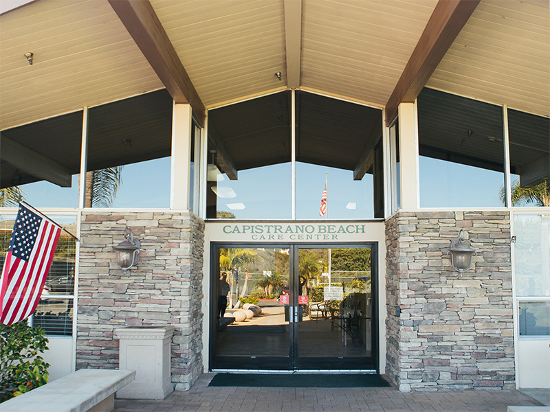 Entrance to the Capistrano Beach Care Center facility with double glass doors and stone wall on either side.