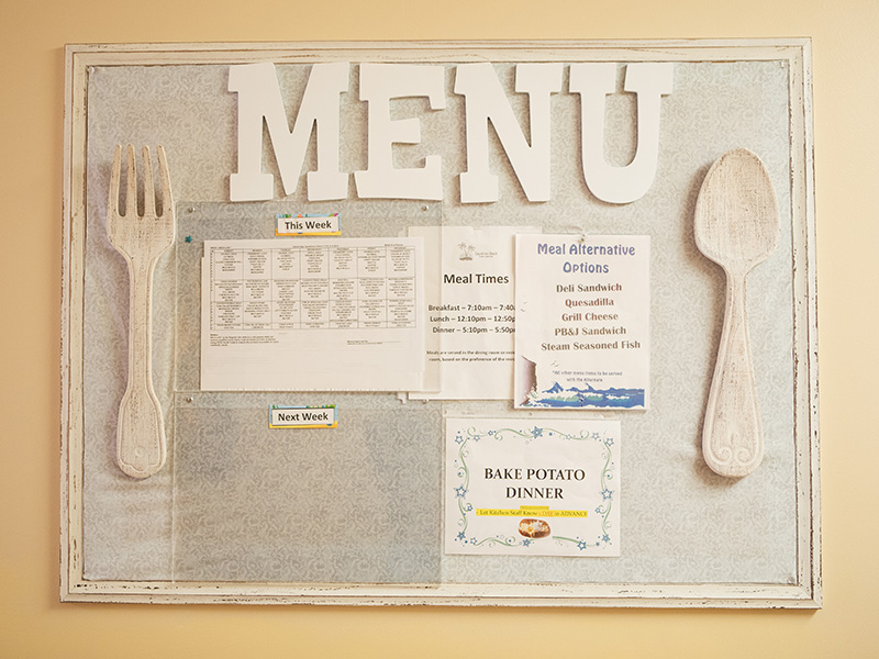 Menu board with a spoon and fork and the menu options listed for the week.