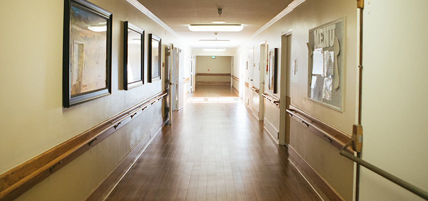 Resident hallway with clean wood floors and handicap railing.