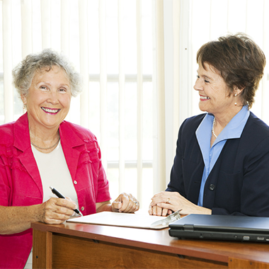 smiling senior woman in a bright pink shirt signing paperwork in an office