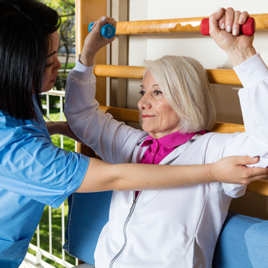 Woman lifting small weights and being assisted by an exercise trainer