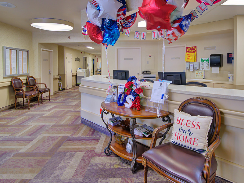 Chairs beside the nurses station with balloons and a Bless our Home pillow.