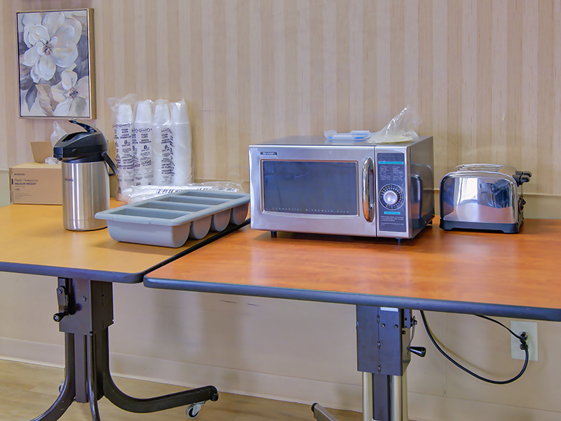 A microwave and toaster on a table with coffee.