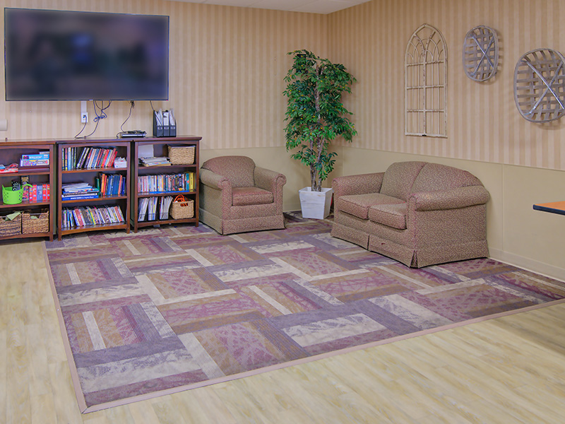 Lobby area with books and a television on the wall.