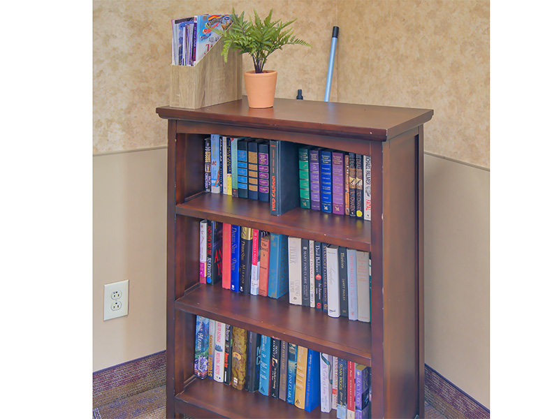 A book case with books nicely organized on the shelves.