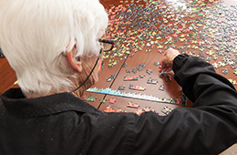 A woman putting together a large puzzle