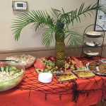 the food table at the luau with a pineapple sculpture and fruit tray