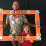 Luau party frame and family members having fun taking pictures