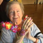 resident wearing a flower lei with body painting on her hand