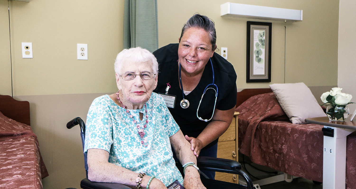 Nurse with a resident in a wheel chair smiling
