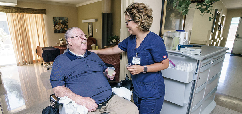 A resident laughing with a nurse as she assists him in taking his medication
