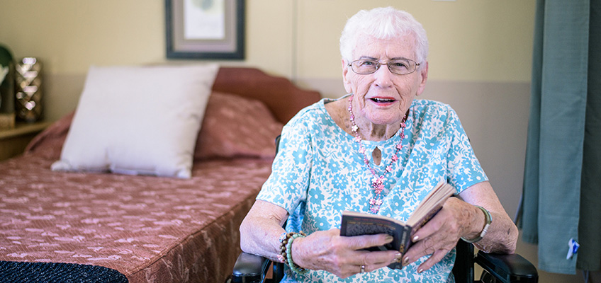 Resident reading a book in her wheelchair beside her bed