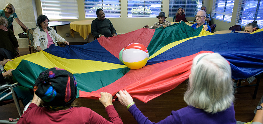 Residents participating in the parachute game with beach balls in the middle