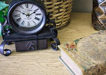 A clock and books by the bedside